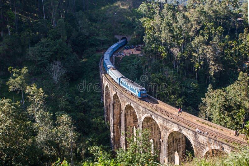 九曲拱桥梁和蓝色火车在斯里兰卡,埃拉 库存图片