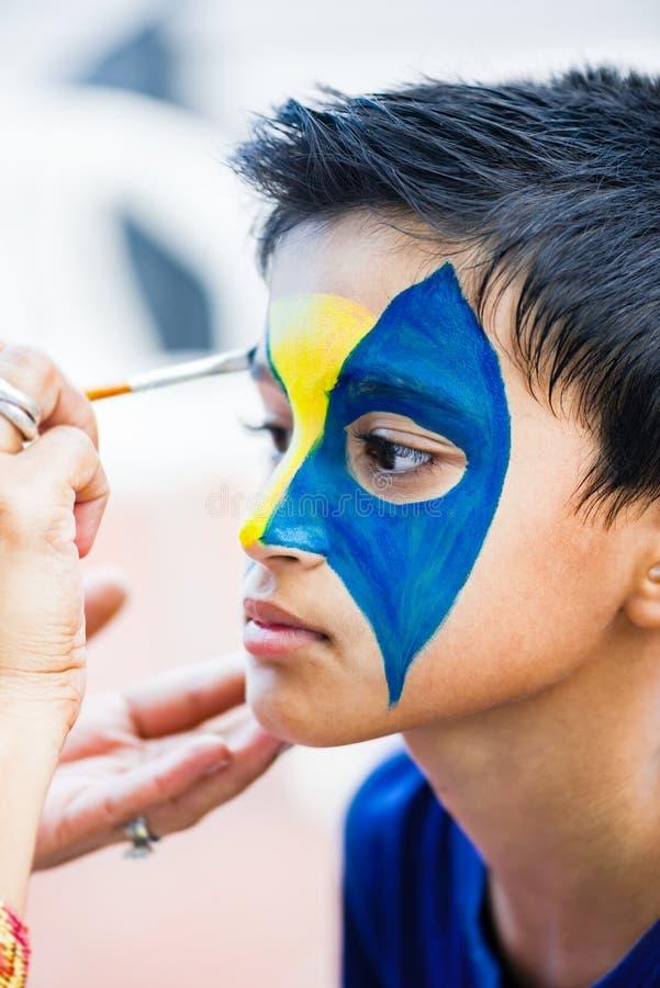 九年的年轻男孩英俊的孩子安排他的面孔被绘为乐趣在生日聚会 免版税库存照片