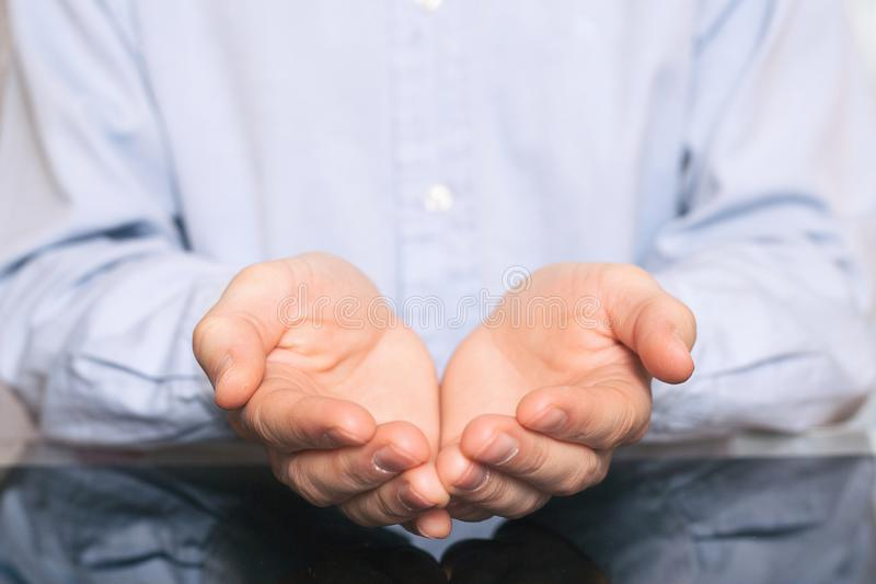 乞求的人标志的开放手 对事负的衬衣的人虚构在他的手棕榈  免版税库存图片