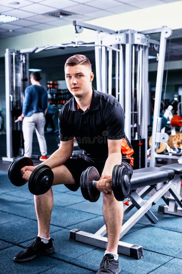 练习一些举重的运动服的英俊的年轻嬉戏人 免版税库存照片