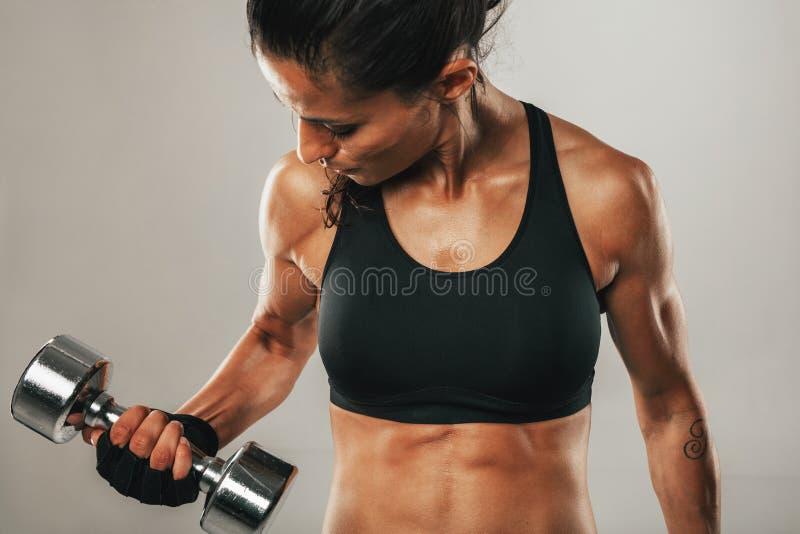 练习举重的坚强的健康少妇 图库摄影