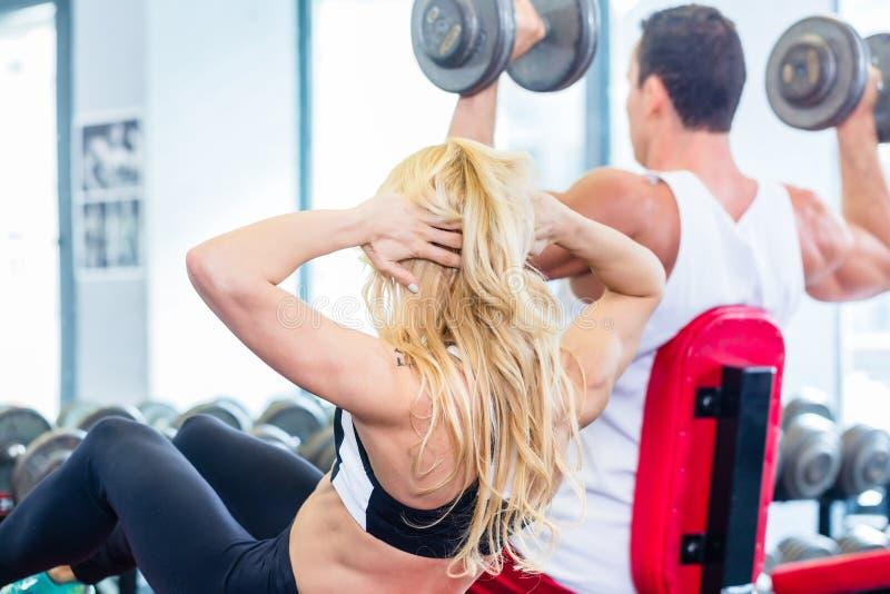 练习在健身健身房的朋友举重 图库摄影