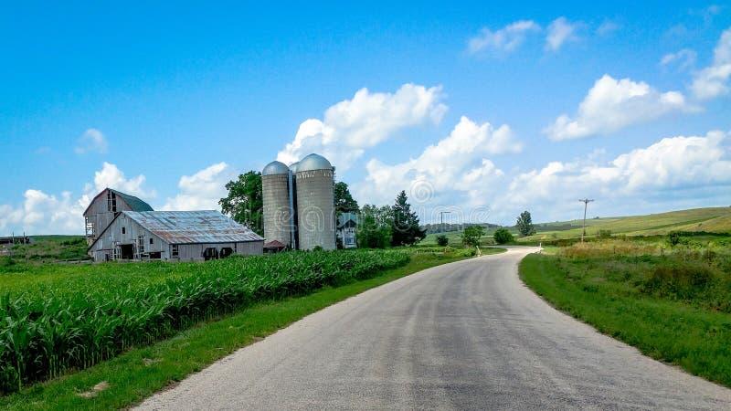 乡下公路在有谷仓和筒仓的威斯康辛 免版税库存图片