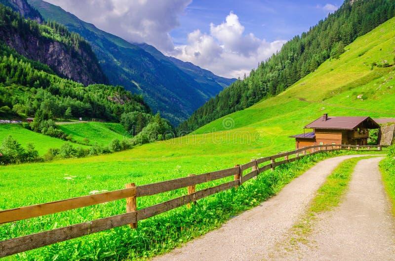 乡下公路导致高山房子的,奥地利 免版税图库摄影