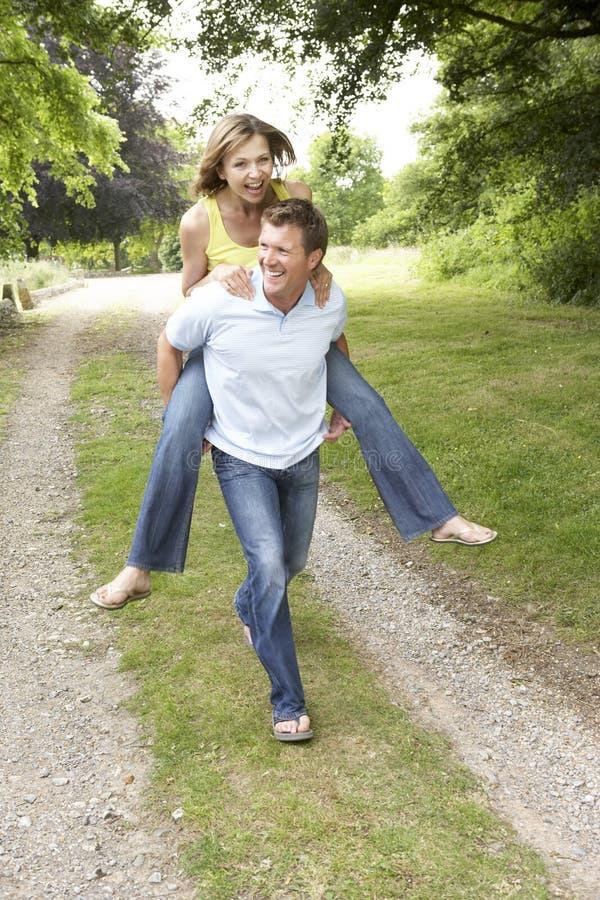 乡下有夫妇的乐趣年轻人 免版税图库摄影