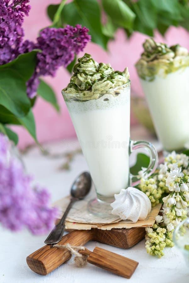 乡村背景中的绿茶抹茶奶饮料 免版税库存图片