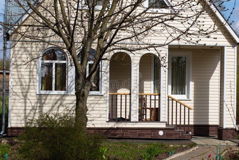 乡间别墅的门面和没有叶子的一棵大树在春天 免版税图库摄影