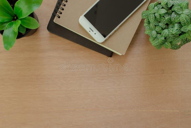 书、智能手机和树罐在土气棕色木书桌上 生活方式工作区,顶视图 库存图片
