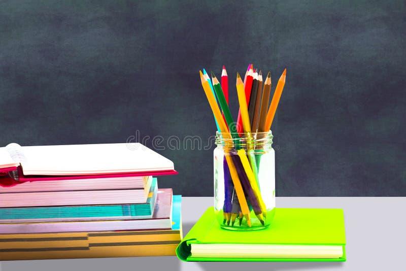书、笔、铅笔和办公设备在蓝色背景,教育和回到课题,裁减路线 免版税库存照片