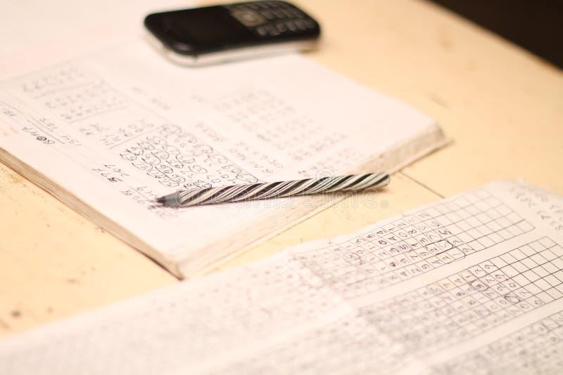 书、笔和手在桌,版本4上打电话 库存图片