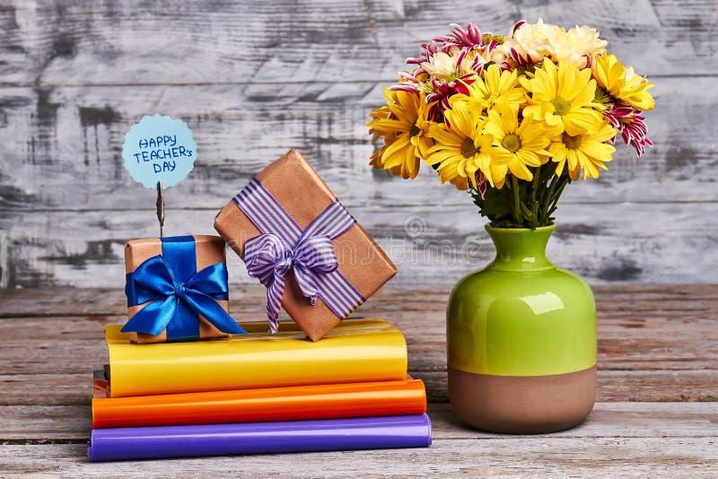 书、花和礼物盒 在木背景的五颜六色的书 免版税图库摄影