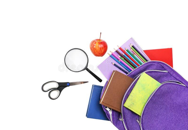 书、苹果、在白色和铅笔隔绝的寸镜、背包 免版税库存照片