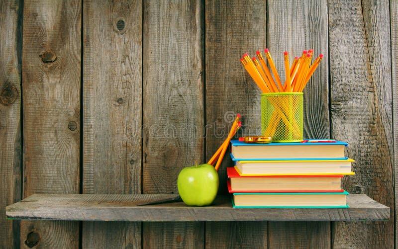 书、苹果和铅笔在一个木架子 免版税库存照片