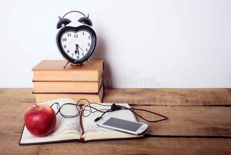 书、闹钟、笔记薄、手机和苹果在木背景 免版税图库摄影