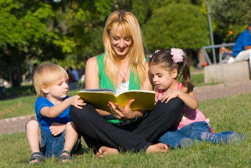 书儿童沼地母亲读 免版税库存图片
