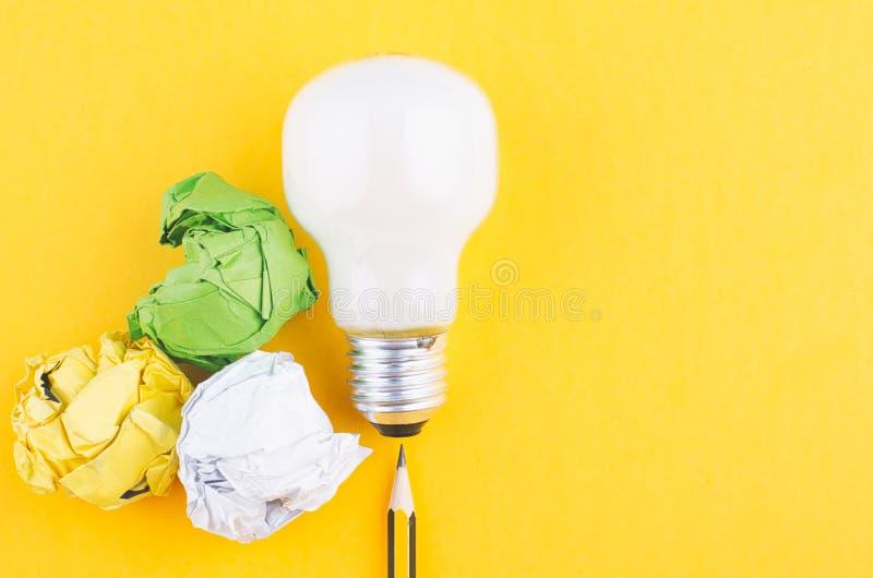 书写,压皱纸和电灯泡在黄色背景 库存照片