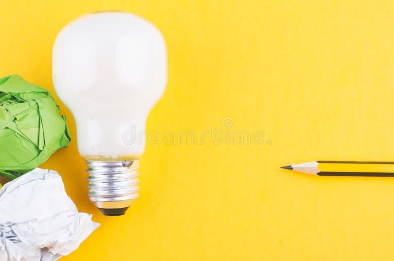 书写,压皱纸和电灯泡在黄色背景 免版税图库摄影