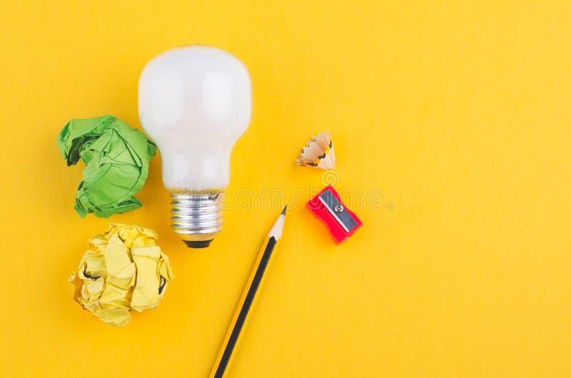 书写,压皱纸和电灯泡在黄色背景 免版税库存照片