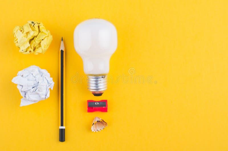 书写,压皱纸和电灯泡在黄色背景 免版税库存图片