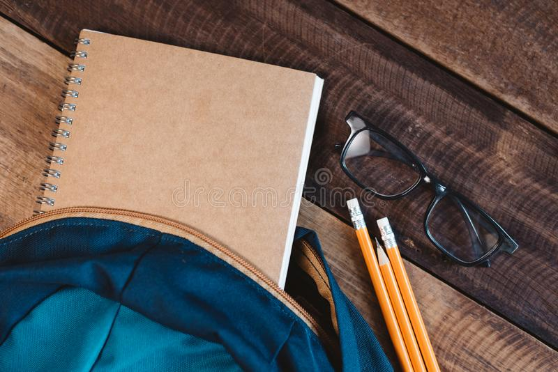 书包、笔记本、铅笔、笔和镜片在一张木桌上 免版税图库摄影