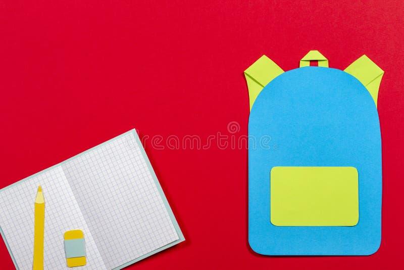 书包背包、笔记本和铅笔纸在红色背景切开了 库存图片