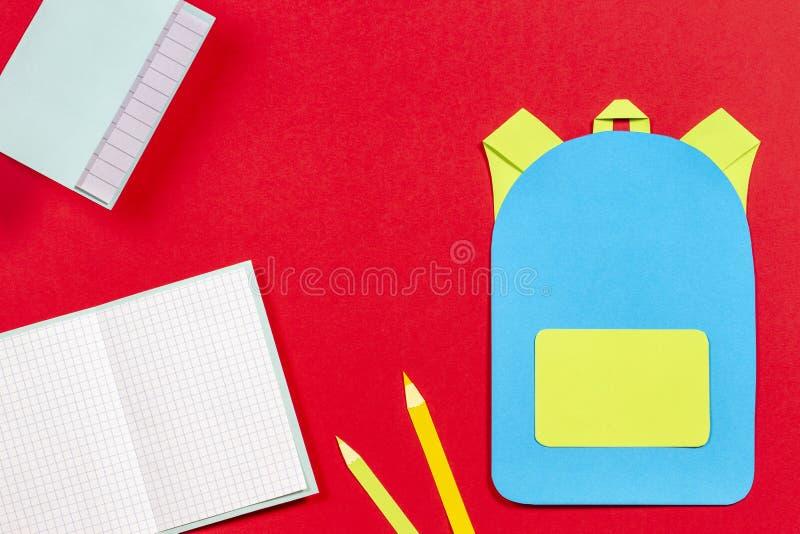 书包背包、笔记本和铅笔纸在红色背景切开了 库存照片