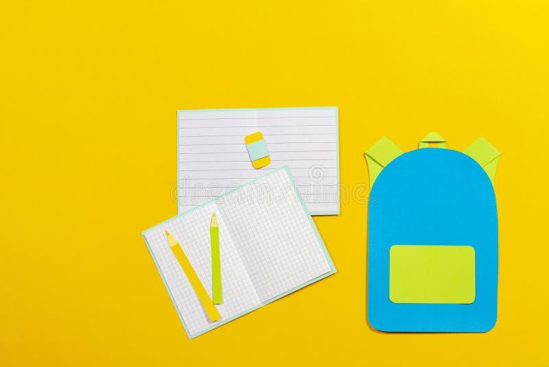 书包背包、笔记本和铅笔纸在黄色背景切开了 免版税库存图片