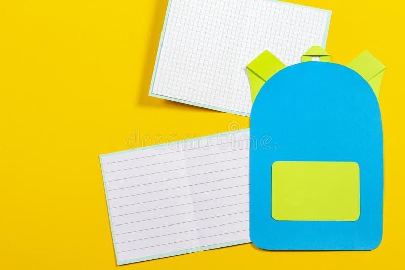 书包背包、笔记本和铅笔纸在黄色背景切开了 库存图片
