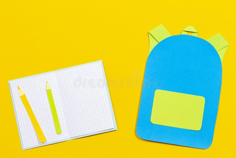 书包背包、笔记本和铅笔纸在黄色背景切开了 免版税库存照片
