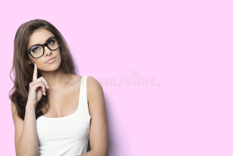 戴书呆子眼镜的想法的妇女在桃红色背景 免版税库存图片