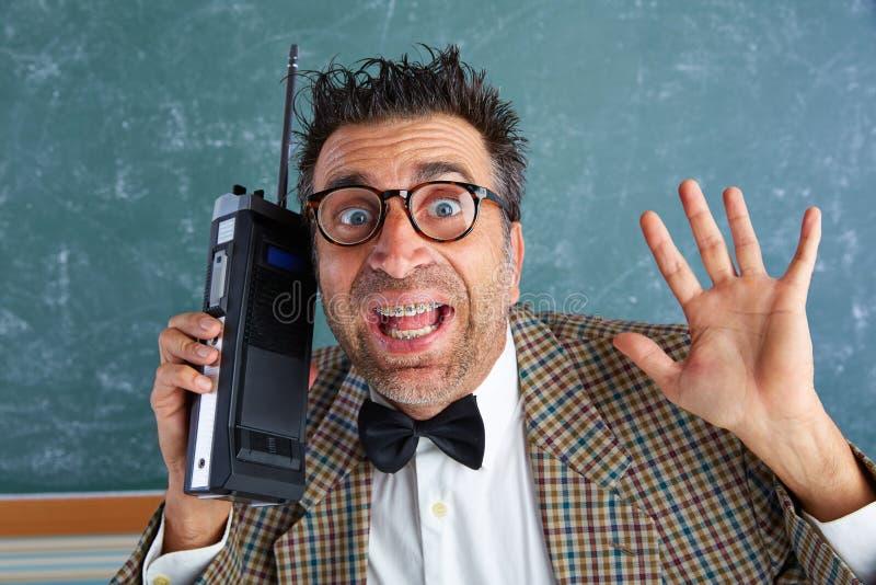 书呆子傻的私家侦探减速火箭的携带无线电话 免版税库存照片