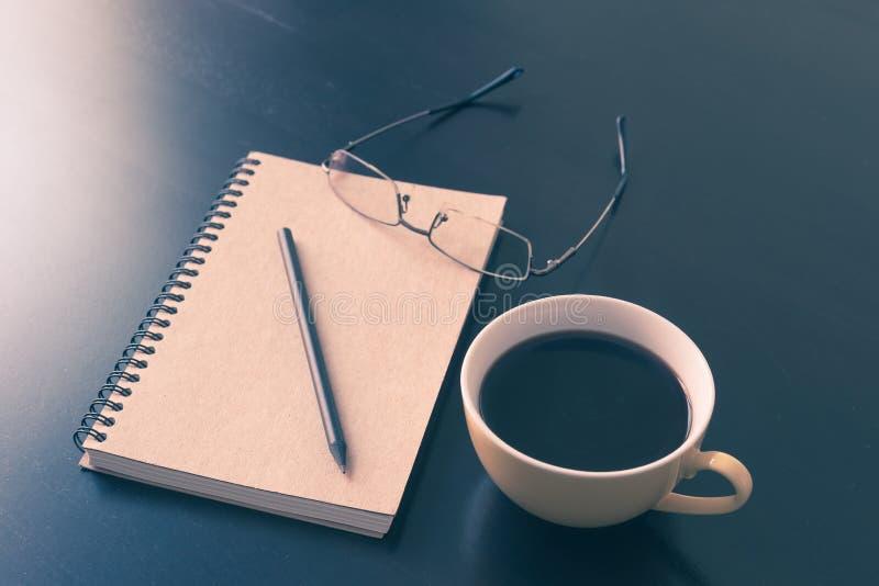 书和咖啡杯在黑木桌上 免版税库存图片