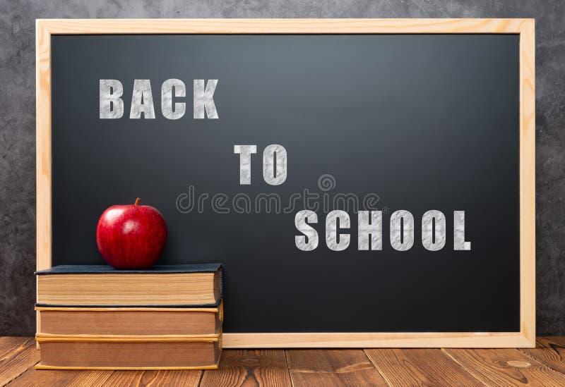 书和苹果在黑板写与回到学校,词前面与裁减路线,并且可以直接地被删除 免版税库存图片