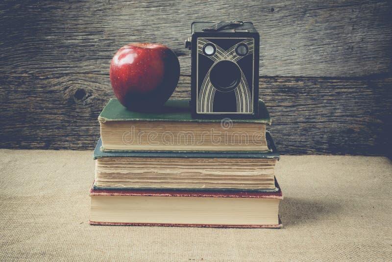 书和葡萄酒照相机用苹果在土气背景与稀土 免版税库存图片
