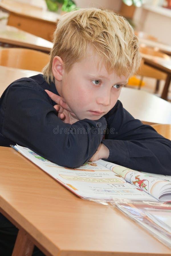 书哀伤的男小学生 免版税库存照片
