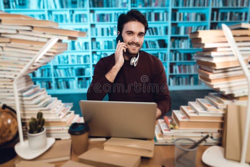 书围拢的白人在图书馆里 学生在电话使用膝上型计算机并且谈话 库存图片