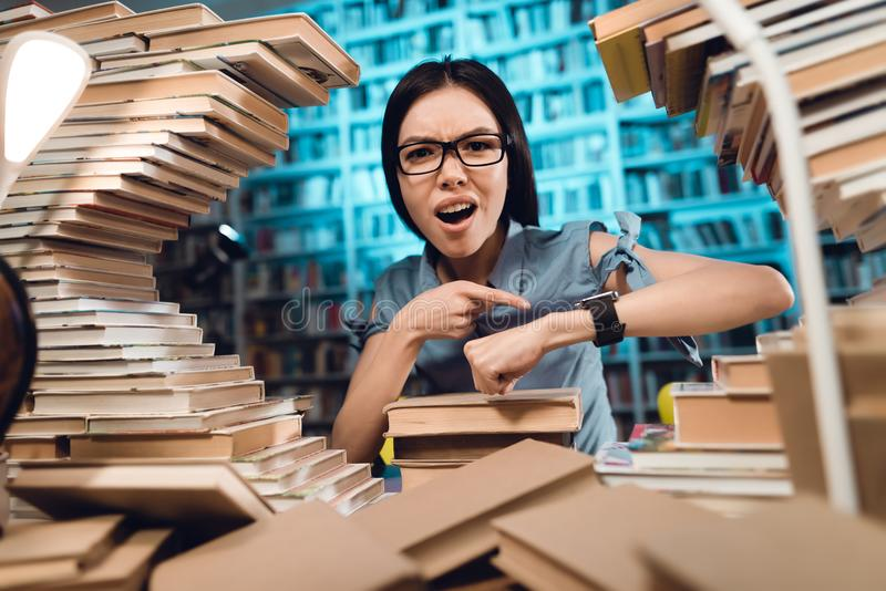 书围拢的种族亚裔女孩在图书馆里在晚上 学生看手表 免版税图库摄影