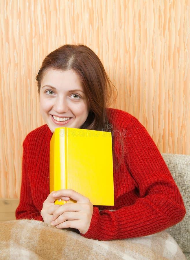 书坐的沙发妇女年轻人 免版税库存照片