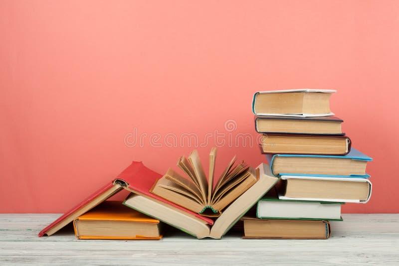 书堆积 打开书、精装书书在木桌上和桃红色背景 回到学校 复制文本的空间 库存图片