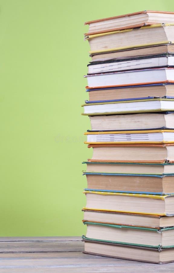 书堆积 打开在木桌和绿色背景上的精装书书 回到学校 复制广告文本的空间 库存照片