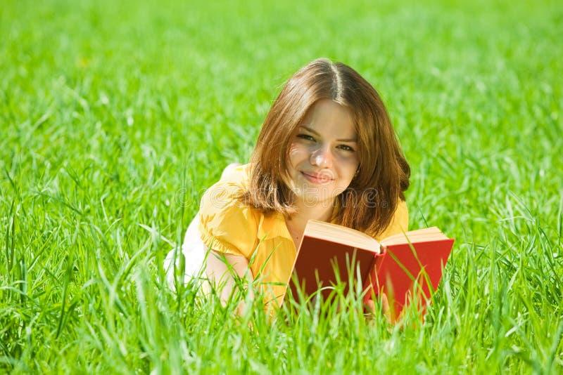 书女孩草读取 库存照片