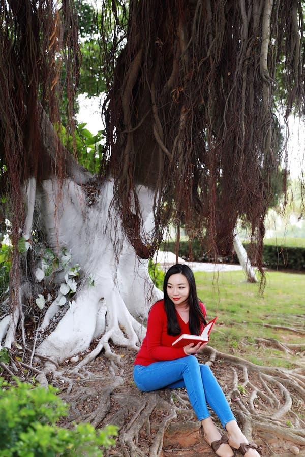 书女孩读取 有书的白肤金发的美丽的年轻女人坐在树下 室外 晴朗的日 免版税库存图片