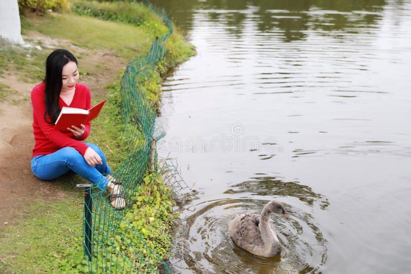 书女孩读取 有书的白肤金发的美丽的年轻女人坐湖边 室外 晴朗的日 免版税库存照片