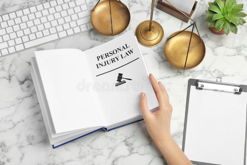 书妇女转动的页与词人身受伤法律的在桌上 免版税图库摄影