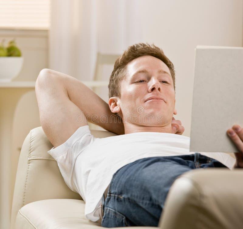 书家庭人读取沙发年轻人 免版税库存图片