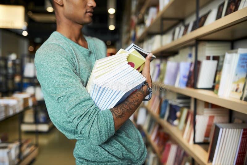 书店工作者在手上的拿着许多书 库存图片