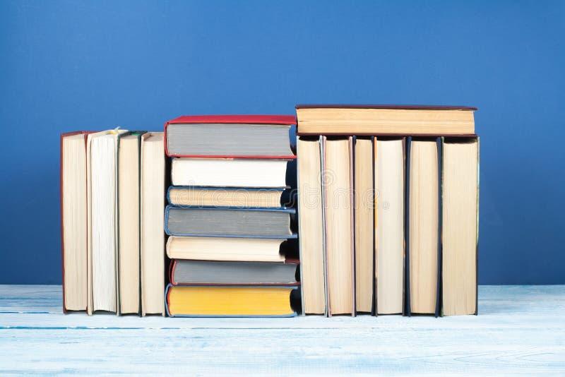 书架、精装书五颜六色的书在木桌上和蓝色背景 回到学校 复制文本的空间 教育 图库摄影