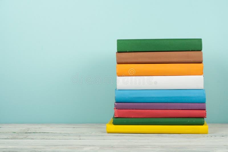 书架、精装书五颜六色的书在木桌上和蓝色背景 r r ?? 图库摄影