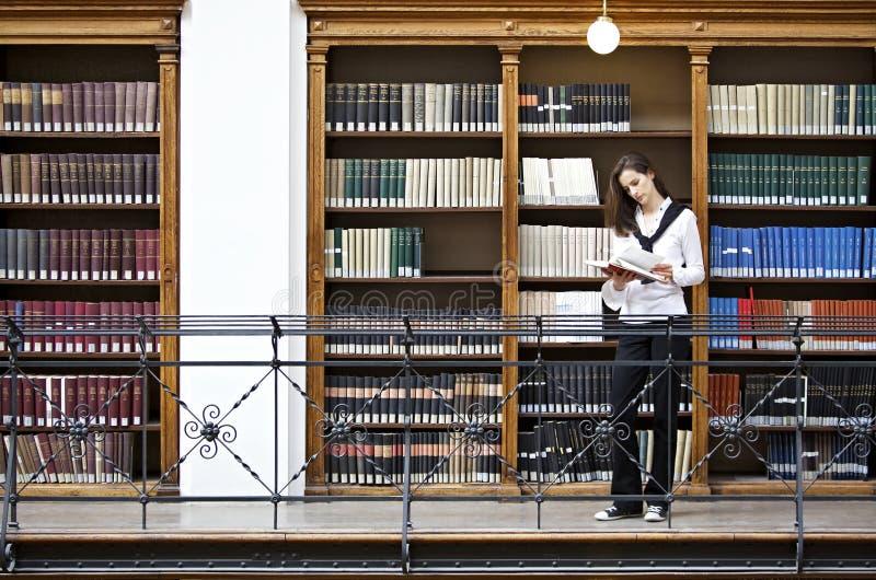 书架前读取妇女 图库摄影