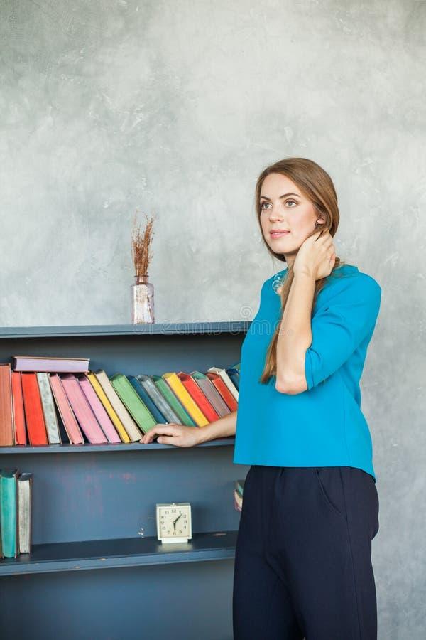书架背景的少妇 免版税库存照片